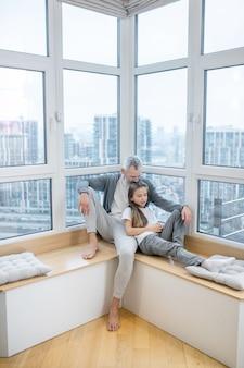 Zrozumienie. dorosły siwy uważny tata przytulający długowłosą córkę w wieku szkoły podstawowej na wakacjach w domu na parapecie dużego okna