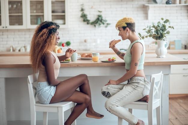 Zrozumienie. dwie młode słodkie szczęśliwe dziewczyny siedzą naprzeciw siebie, jedząc spokojnie lekkie śniadanie w domu