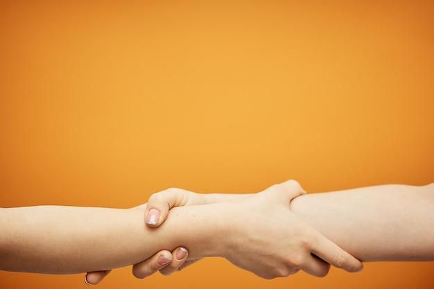 Zrozumienie i porozumienie, uścisk dłoni na pomarańczowo.