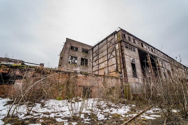 Zrujnowana fabryka lub opuszczona hala magazynowa z wybitymi oknami i drzwiami na zewnątrz w zimie.