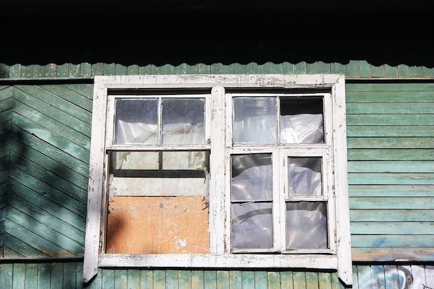 Zrujnowany drewniany opuszczony dom. stary budynek. dom niezamieszkany. zabite deskami okno i nikogo tam nie ma. zbliżenie rozbitego okna.