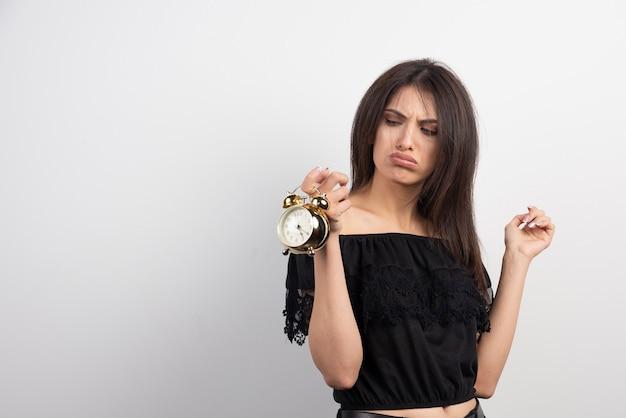 Zrzędliwa kobieta trzyma zegar