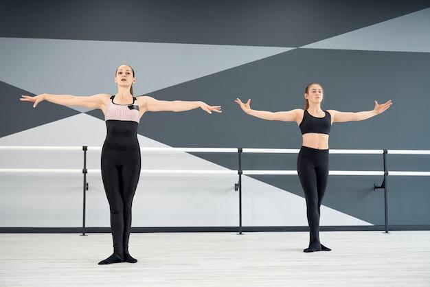 Zsynchronizowana instruktorka i dziewczyna w nauce ruchów