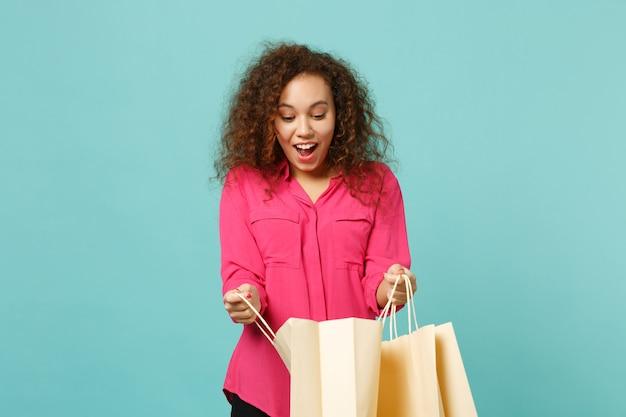 Zszokowana afrykańska dziewczyna w różowe ubrania dorywczo trzymając worek z zakupami po zakupach na białym tle na tle niebieskiej ściany turkus. koncepcja życia szczere emocje ludzi. makieta miejsca na kopię.