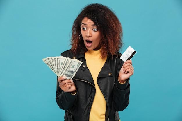 Zszokowana afrykańska kobieta trzyma kredytową kartę w skórzanej kurtce