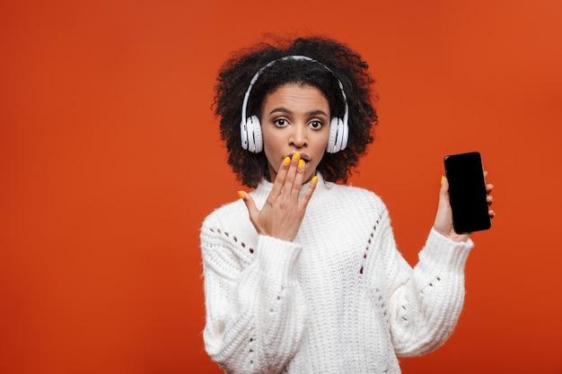 Zszokowana, atrakcyjna młoda afrykańska kobieta w bezprzewodowych słuchawkach, stojąca na białym tle nad czerwoną ścianą, pokazująca pusty ekran telefonu komórkowego