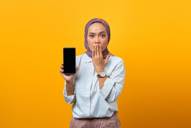 Zszokowana azjatka pokazująca pusty ekran smartfona na żółtym tle
