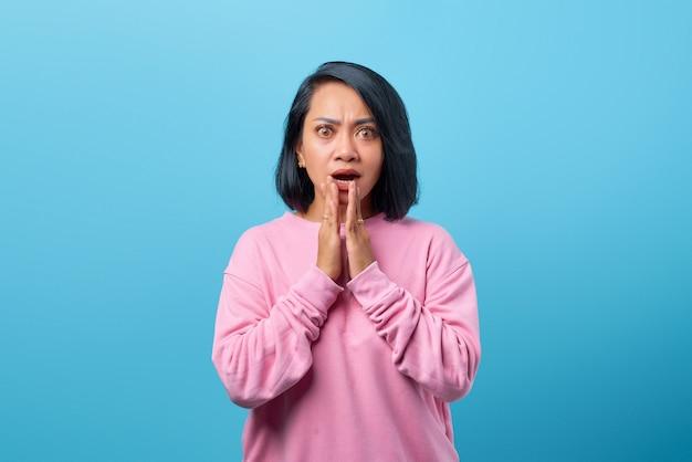 Zszokowana azjatka zakrywająca usta dłonią na niebieskim tle