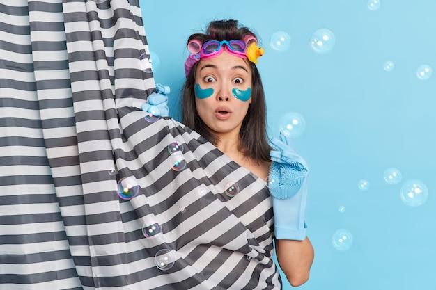 Zszokowana azjatka zaskoczona, gdy ktoś wszedł do łazienki, gdy brała prysznic, chowa swoje nagie ciało poddawanym zabiegom upiększającym, sprawia, że fryzura pozuje w pomieszczeniu wokół baniek mydlanych. koncepcja higieny