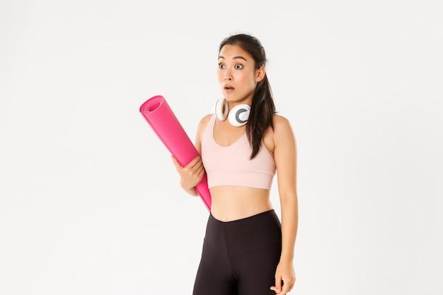 Zszokowana azjatycka fitness dziewczyna w odrętwieniu, opadająca szczęka i dysząca, patrząc w lewo na logo lub informacje o banerze, trzymając gumową matę do ćwiczeń fitness.
