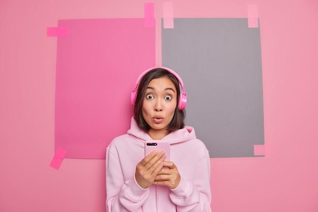 Zszokowana azjatycka nastolatka korzysta z najnowszych bezprzewodowych słuchawek, korzysta z mobilnej aplikacji muzycznej, słucha ścieżki dźwiękowej, słyszy zaskakujące wiadomości, ubrana swobodnie, odizolowana na różowej ścianie