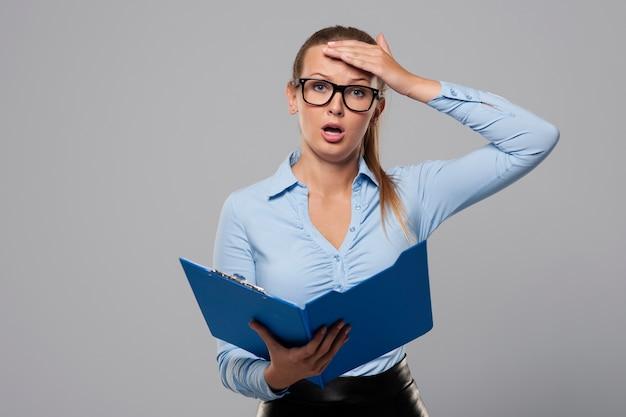 Zszokowana bizneswoman popełnia błąd w dokumentach biurowych