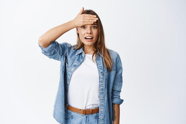 Zszokowana blond dziewczyna uderza się w czoło i wpatruje się w przód, pamiętaj lub zapominaj o czymś złym, wyglądając na zmartwioną, stojąc w zwykłych ubraniach na białej ścianie