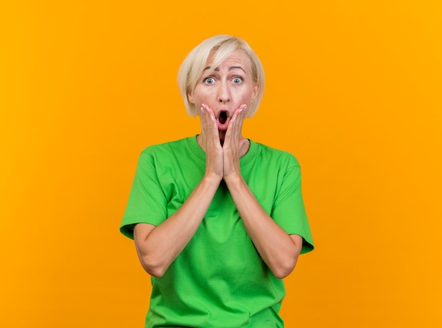 Zszokowana blondynka słowiańska blondynka w średnim wieku patrząc na kamery, trzymając ręce na twarzy na białym tle na żółtym tle z miejsca na kopię