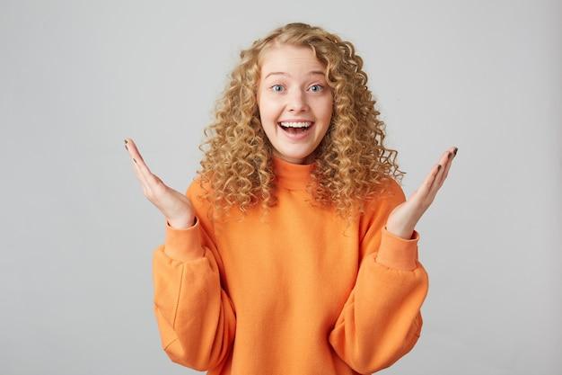 Zszokowana blondynka z kręconymi włosami i niebieskimi oczami patrząc z przodu, trzymając dłonie do góry, odizolowane na białej ścianie