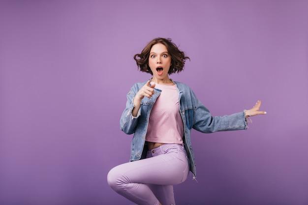Zszokowana brązowooka kobieta skacząca. radosna krótkowłosa dziewczyna w tańcu kurtki.