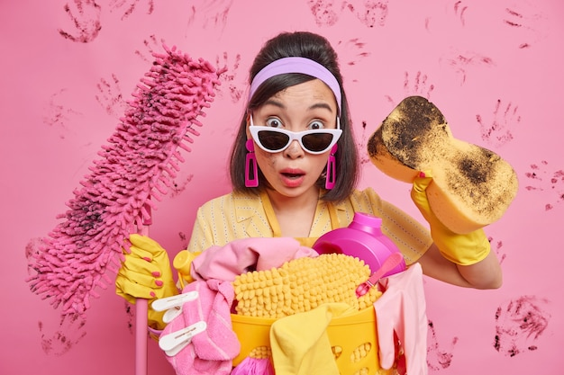 Zszokowana, brudna kobieta zszokowana widokiem bałaganu, zabłoconego pokoju, w którym trzyma gąbkę i mopa, nosi modne okulary przeciwsłoneczne ochronne gumowe rękawiczki izolowane na różowej ścianie