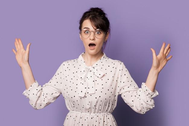 Zszokowana brunetka gestykuluje rękami pozuje z otwartymi ustami na fioletowej ścianie studia