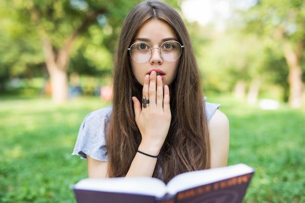 Zszokowana brunetka kobieta siedzi w parku trzymając książkę i patrząc w kamerę