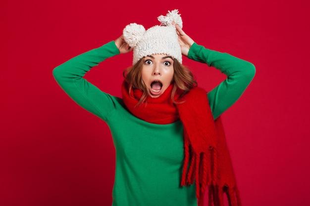 Zszokowana brunetka kobieta w swetrze, zabawny kapelusz i szalik