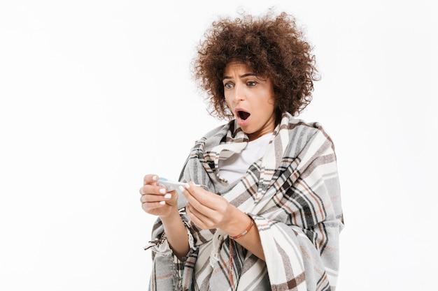 Zszokowana chora kobieta owinięta w koc patrząc na termometr