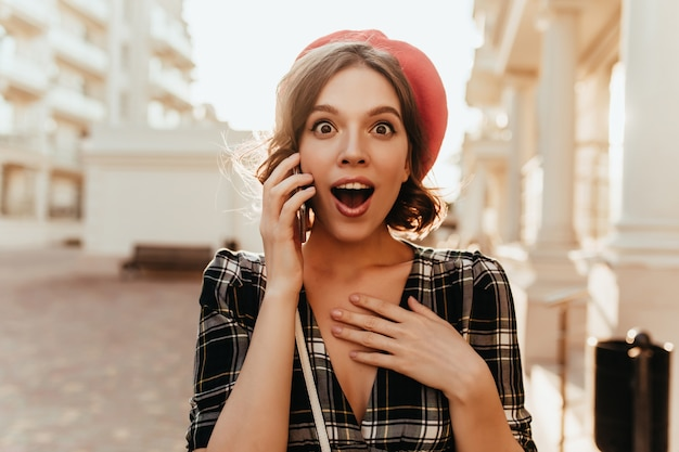 Zszokowana ciemnooka dziewczyna z pięknym uśmiechem stojąca na ulicy. francuski kręcone kobieta rozmawia przez telefon w słoneczny dzień.
