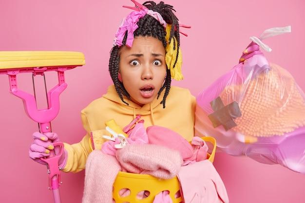 Zszokowana ciemnoskóra kobieta z dredami sprząta w domu