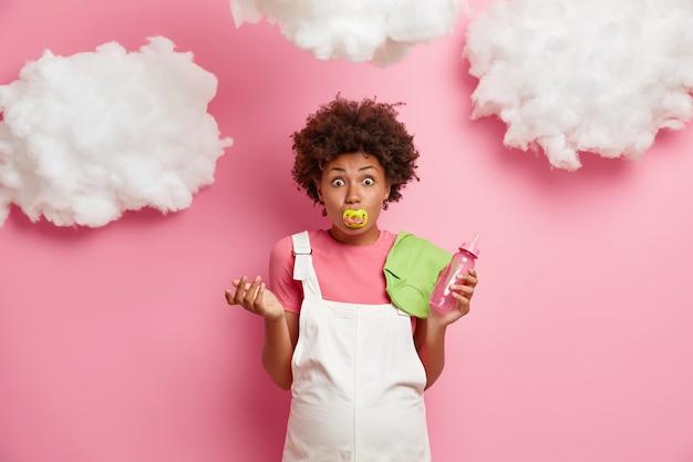 Zszokowana ciężarna trzyma sutek w ustach, trzyma butelkę do karmienia dziecka i podkoszulka, nosi sarafan, przygotowuje się do porodu, lubi komunikować się z nienarodzonym dzieckiem. oczekiwanie i macierzyństwo