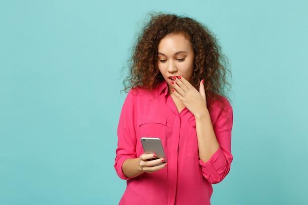 Zszokowana dziewczyna afryki w ubranie obejmujące usta ręką za pomocą telefonu komórkowego pisania wiadomości na białym tle na niebieskim tle turkus. ludzie szczere emocje, koncepcja stylu życia. makieta miejsca na kopię.