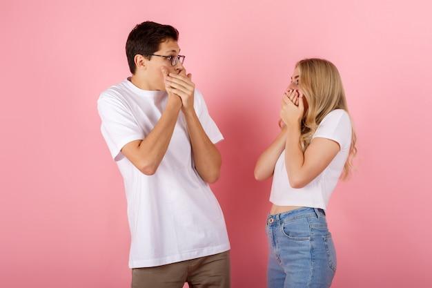 Zszokowana dziewczyna i chłopak zakrywają usta i patrzą na siebie