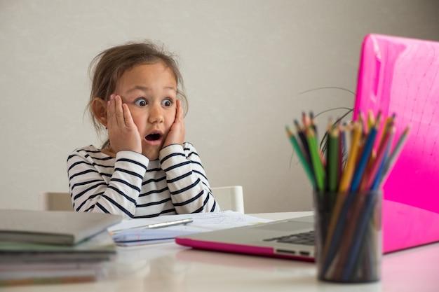 Zszokowana dziewczyna odrabiania lekcji w domu