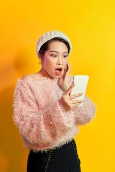 Zszokowana dziewczyna patrząc na ekran telefonu z otwartymi ustami. zewnątrz portret zaskoczony młoda kobieta ubrana w różowe futro i trzymając smartfon.