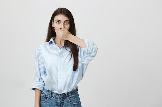 Zszokowana dziewczyna patrzy i zakrywa usta ręką