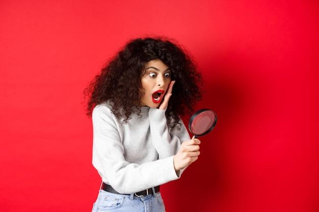 Zszokowana dziewczyna patrzy przez szkło powiększające z opuszczoną szczęką i widzi coś niesamowitego stojącego na czerwonym...