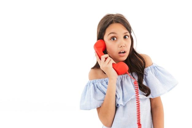 Zszokowana dziewczyna rozmawia przez telefon.