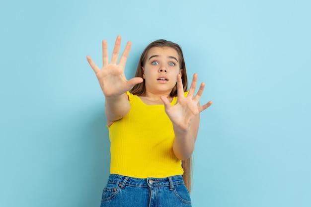 Zszokowana dziewczyna ubrana w dżinsy i żółtą bluzkę