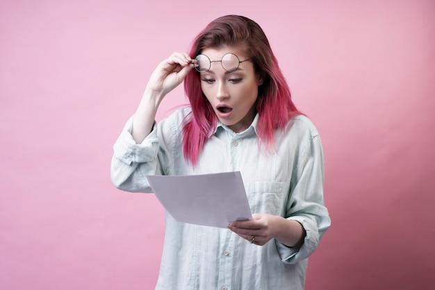 Zszokowana dziewczyna w okularach i papierze