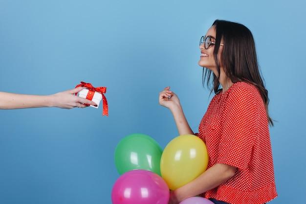 Zszokowana dziewczyna w okularach patrzy na mały prezent przed nią