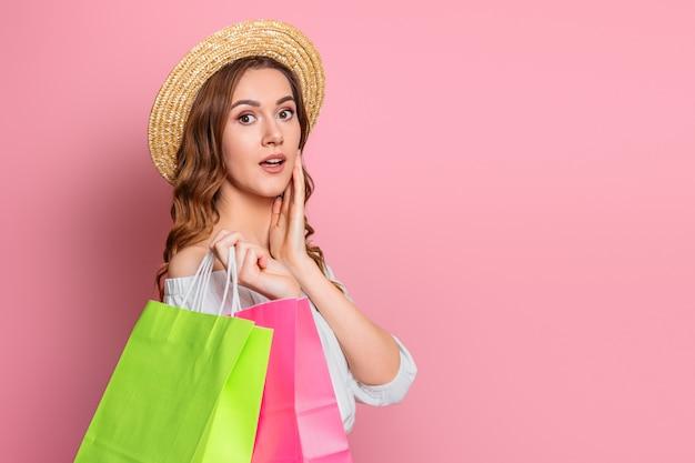 Zszokowana dziewczyna w słomkowym kapeluszu i białej letniej sukience trzyma torby na zakupy w rękach na różowej ścianie. zaskoczony podekscytowana dziewczyna daje prezenty koncepcja baner sprzedaży internetowej