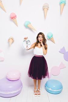 Zszokowana dziewczyna w spódnicy midi zdała sobie sprawę, że goście spóźnili się na jej przyjęcie urodzinowe. pełnometrażowy portret modnej młodej kobiety z budzikiem i nieszczęśliwą miną, pozowanie w pobliżu słodyczy zabawek.
