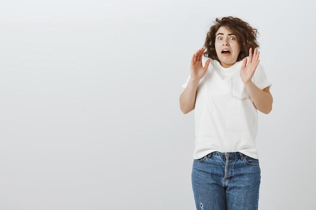 Zszokowana dziewczyna z zasadzką skacząca przestraszona i unosząca ręce w górę zaskoczona