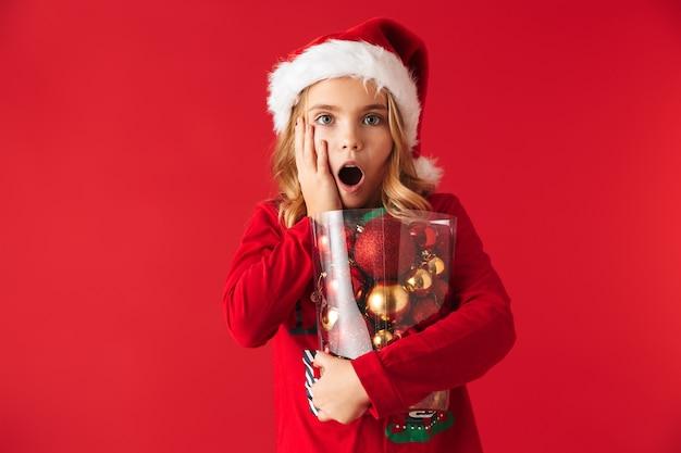 Zszokowana dziewczynka ubrana w strój świąteczny stojący na białym tle, trzymając zestaw zabawek choinki