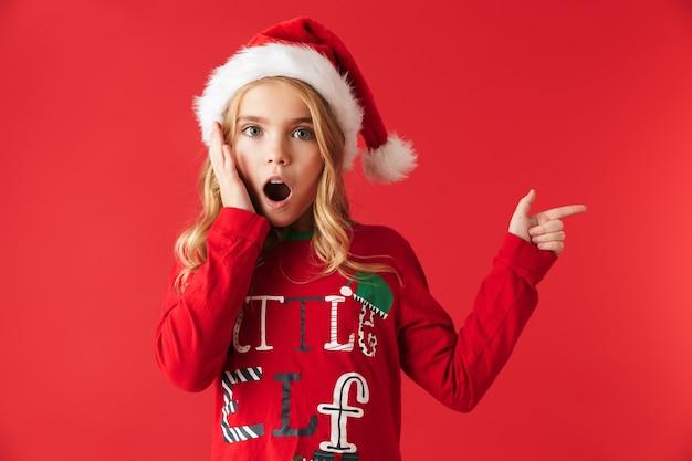 Zszokowana dziewczynka ubrana w świąteczny kostium stojący na białym tle, wskazując