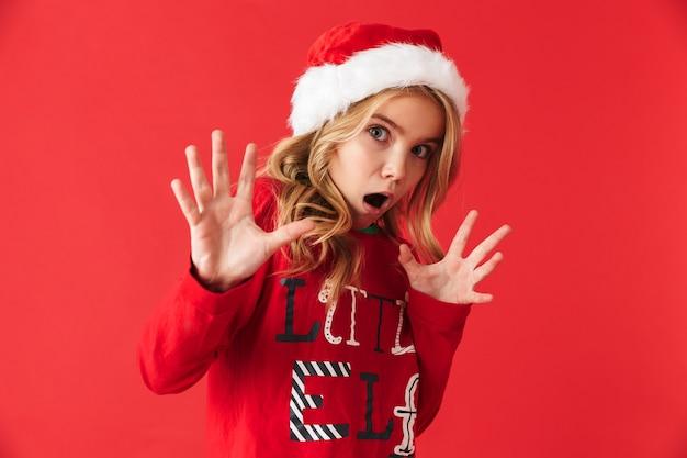 Zszokowana dziewczynka ubrana w świąteczny kostium stojący na białym tle