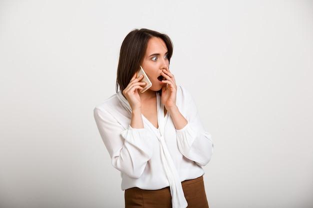 Zszokowana elegancka kobieta rozmawia przez telefon, plotkuje