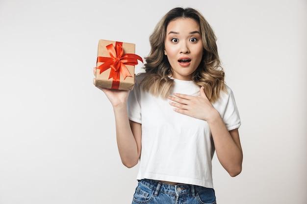 Zszokowana emocjonalna urocza młoda kobieta pozuje na białym tle nad białą ścianą ściana trzymająca pudełko prezentowe