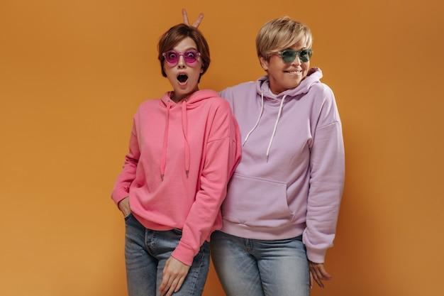 Zszokowana fajna dziewczyna w okularach przeciwsłonecznych i różowych bluzach z kapturem, patrząc w kamerę i kobieta o blond włosach pokazująca znak pokoju na pomarańczowym tle.