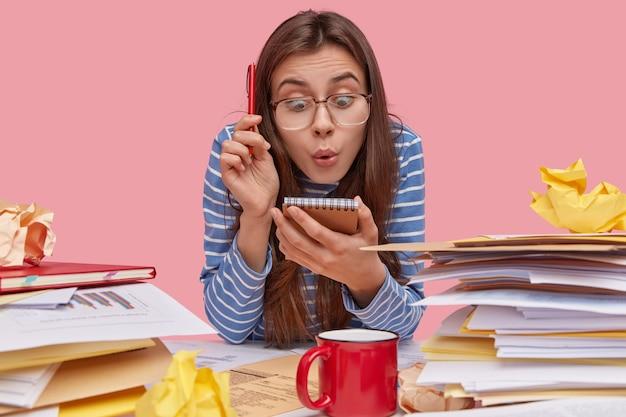 Zszokowana, fuuny młoda kobieta wonk wpatruje się w zeszyt, nosi długopis, ma stosy papierów na miejscu pracy, nosi okulary i ubrania w paski