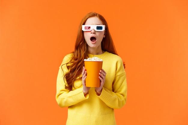 Zszokowana i napięta ruda kobieta widzi intensywną walkę na ekranie podczas oglądania filmu