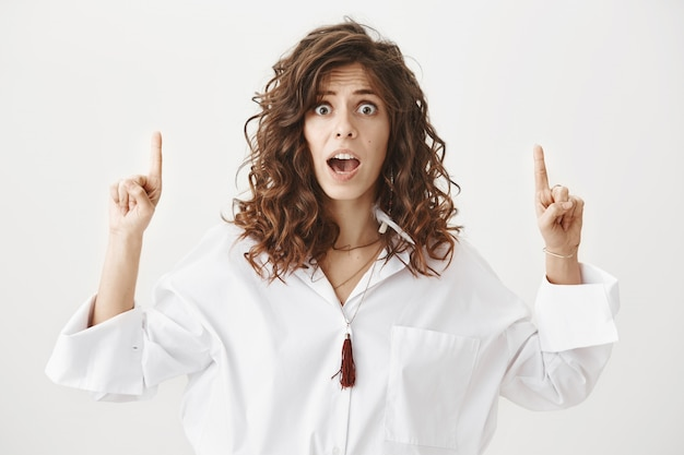 Zszokowana i zaniepokojona kobieta wskazuje palcami w górę